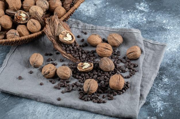 회색 식탁보에 아로마 커피 콩을 넣은 건강한 호두.