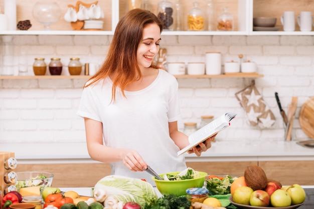 건강한 체중 감소와 영양 균형. 여성 라이프 스타일. 그린 샐러드를 준비하는 젊은 여성. 손에 레시피 책.