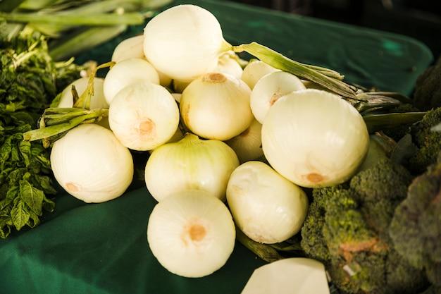 Здоровый белый лук с зеленым овощем на столе на рынке