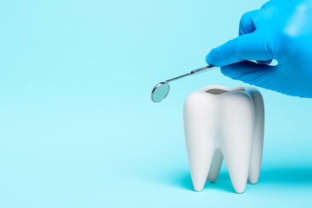 明るい青の背景に青いゴム手袋で医師の手で健康な白い歯と歯科医のミラー。