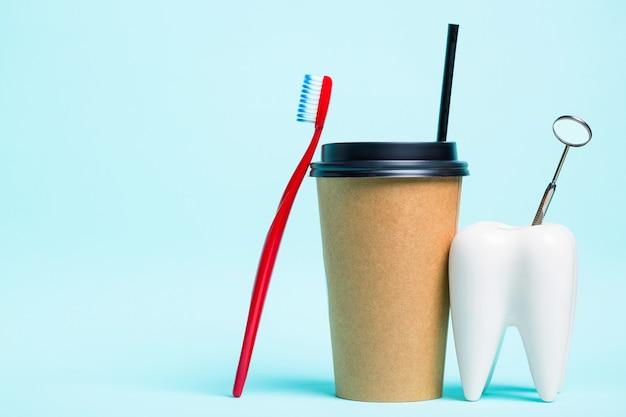 밝은 파란색 배경에 칫솔과 커피의 플라스틱 열 컵 근처 건강한 하얀 치아와 치과 의사 거울