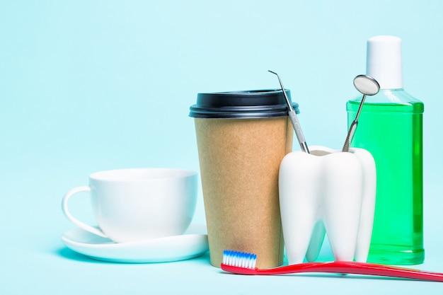 밝은 파란색 배경에 칫솔, 구강 세척제, 차 컵 및 커피의 플라스틱 열 컵 근처 건강한 하얀 치아와 치과 의사 거울