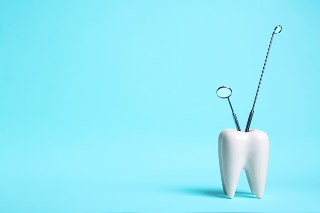 Healthy white tooth and dentist mirrors on light blue background.