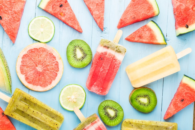 Healthy whole fruit popsicles with berries kiwi watermelon cantaloupe on wooden vintage table