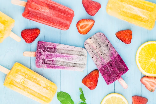 Healthy whole fruit popsicles with berries strawberry orange  dragon fruit  on wooden vintage table