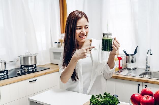健康な女性は、home.dietingコンセプトのキッチンでミキサーで緑の野菜のデトックスクレンジングと緑の果物のスムージーを作ることをお楽しみください。健康的な生活様式