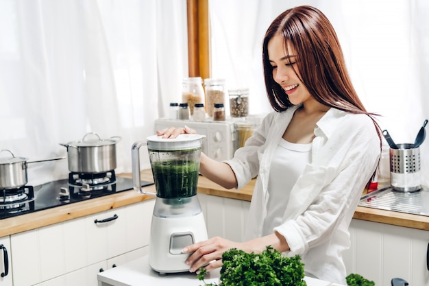 Healthy woman enjoy making green vegetables detox cleanse and green fruit smoothie with blender in kitchen at home.dieting concept. healthy lifestyle