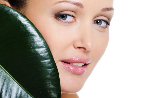 Лицо здоровой женщины с зеленым листом покрывает ее лицо красоты