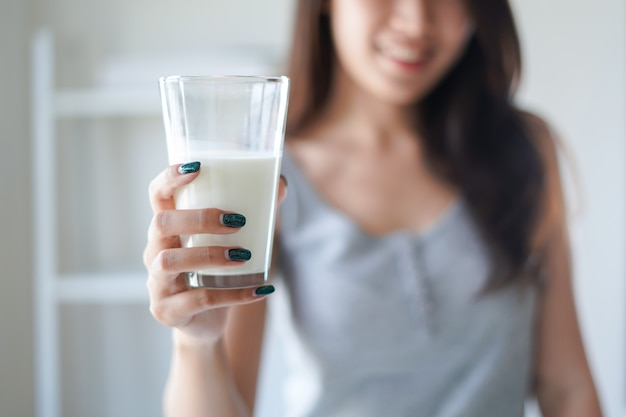 Healthy woman holds a glass of milk