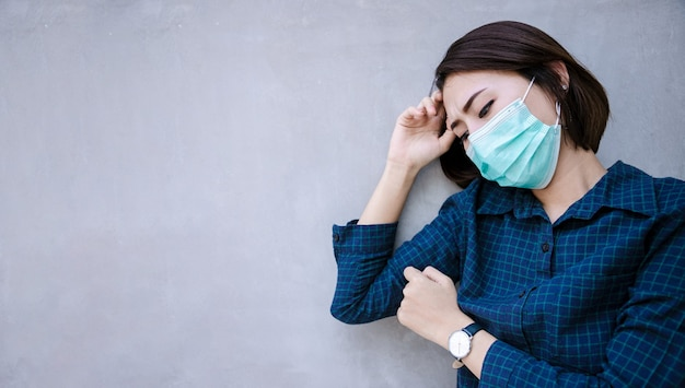 Здоровая женщина в зеленой медицинской защитной маске показывая остановку жеста. охрана здоровья и профилактика во время гриппа и инфекционной вспышки или covid-19 в congrete wall