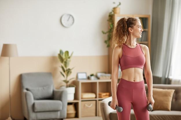 Здоровая женщина в спортивной одежде, упражнения с гантелями в комнате дома