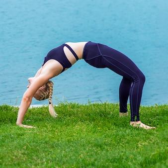 Здоровая женщина растягивается на траве