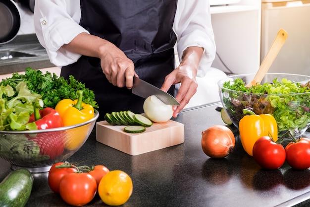 ヘルシーな女性は、オリーブオイル、トマト、サラダなどの野菜サラダを作ります。