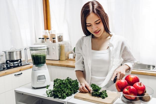 健康な女性はブレンダーで野菜グリーンフルーツのスムージーを作る