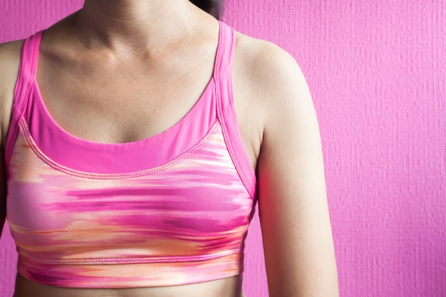 Healthy woman in pink sport bra on pink background, breast cancer awareness