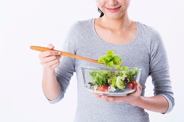 Healthy woman preparing salad