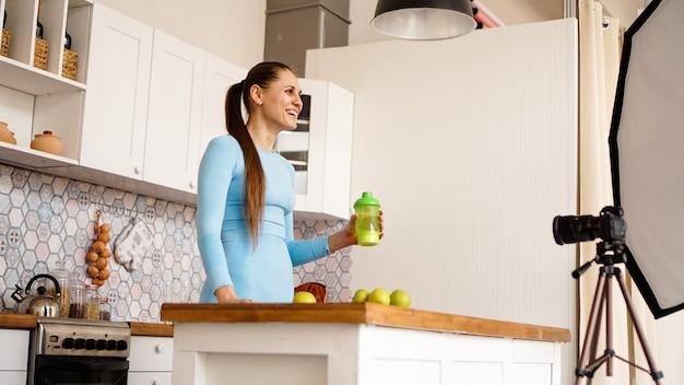 건강한 여성이 부엌에 서서 건강 식품 첨가물에 대한 비디오 블로그를 녹화합니다. 그녀는 스포츠 영양 한 병을 들고 웃고 있다