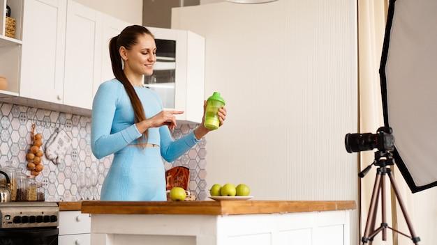 キッチンに立っている間、健康的な食品添加物についての彼女のビデオブログを記録している健康な女性。彼女はスポーツ栄養のボトルを持って笑っています
