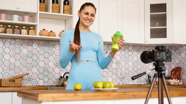 Healthy woman recording her video blog about healthy food additives while standing at kitchen. she is holding a bottle of sports nutrition and smiling