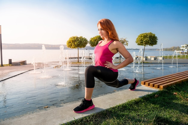 健康な女性が休んで、湖の近くで屋外でストレッチ運動をしています