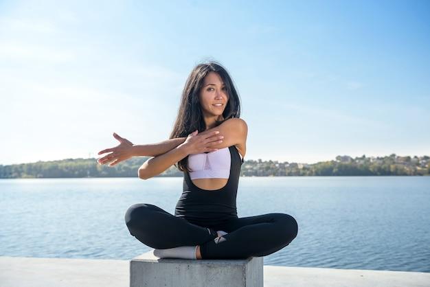 湖の近くで休憩し、屋外でストレッチ運動をしている健康な女性。