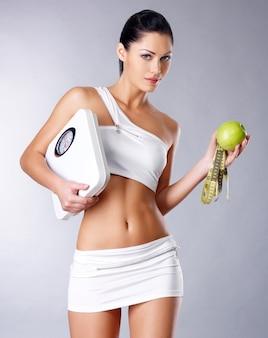 La donna in buona salute sta con le scale e la mela verde. concetto di mangiare sano.