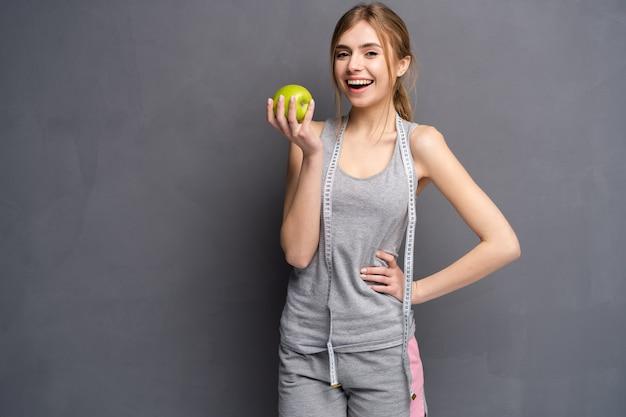 健康な女性は巻尺と青リンゴで立っています