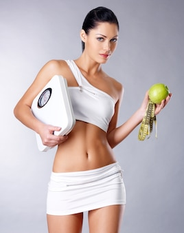 Здоровая женщина стоит с весами и зеленым яблоком. концепция здорового питания.