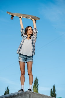 Healthy woman stretching with skateboard in her hand against the sky