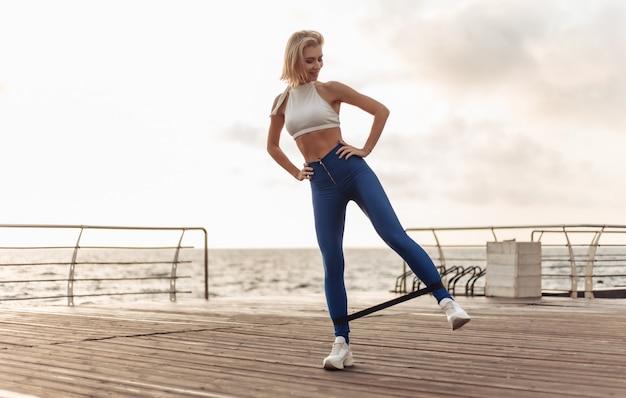 海辺の遊歩道で健康な女性のトレーニングビーチでフィットネスゴムを使って運動をしているスポーツウェアのスポーツウーマン