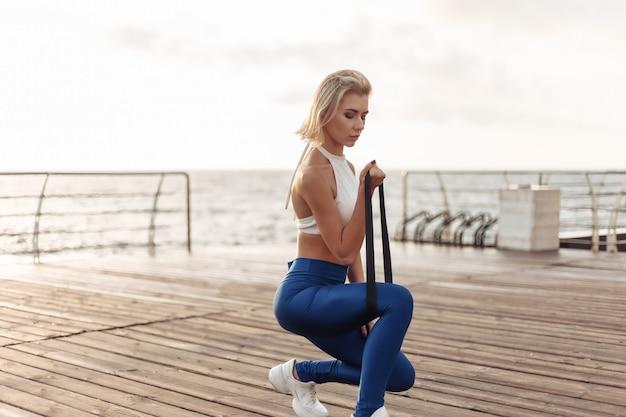 Здоровая женщина тренируется на набережной спортсменка в спортивной одежде делает упражнения с фитнес-резиной