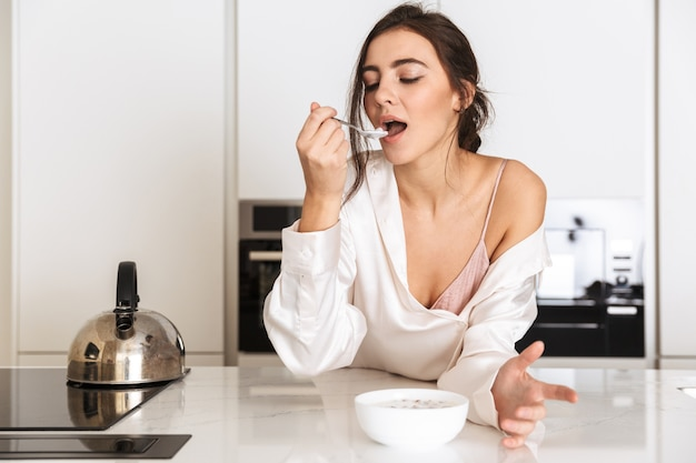 Здоровая женщина в шелковой одежде ест мюсли с молоком во время завтрака в квартире