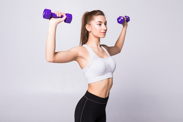 白い壁に隔離されて運動ダンベルを持つ健康な女性。フィットネスジムのコンセプト