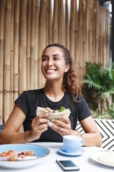 Здоровая женщина с загаром, сидя в футболке на террасе кафе, завтракает и пьет кофе.