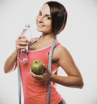 Здоровая женщина с водой и яблочной диетой, улыбаясь, изолирована на белом