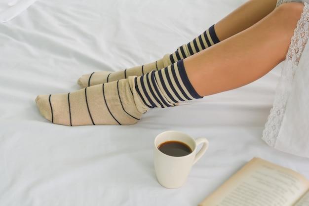 健康な女性と朝のベッドの上にコーヒーを入れる