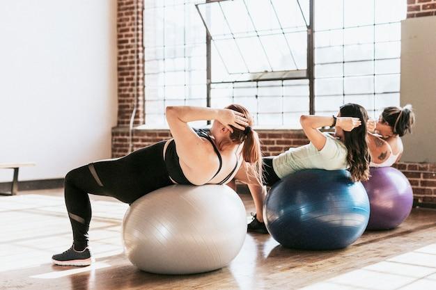 腹筋運動にフィットネスボールを使用している健康な女性