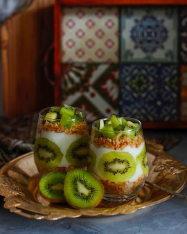 Healthy yogurt dessert with granola and fresh cut kiwi in tall glasses.