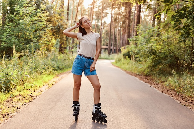 Healthy young adult dark haired woman wearing beige t shirt and jeans shirt riding on roller skates on asphalt road in park, enjoying active ti,e, keeps eyes closed.