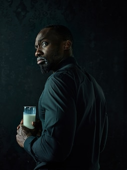 Healthy young african man holging cup of milk on a bllack studio.