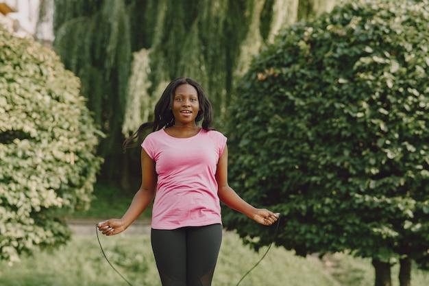 朝の屋外で健康な若いアフリカの女性。ロープを持つ少女。