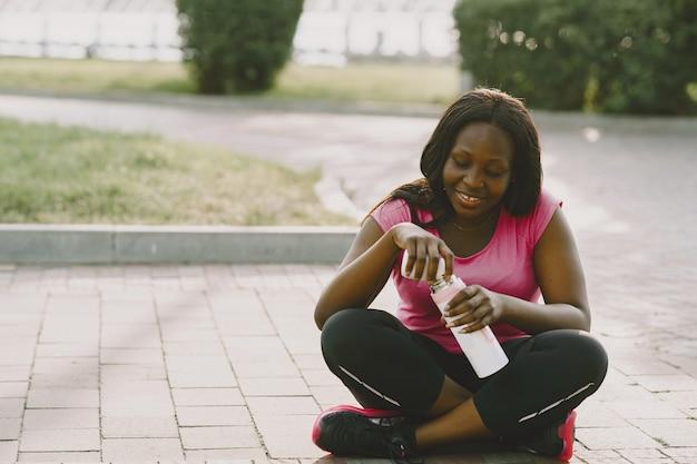 朝の屋外で健康な若いアフリカの女性。水のボトルを持つ少女。