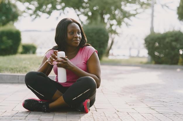 Здоровая молодая африканская женщина на открытом воздухе утром. девушка с бутылкой воды.