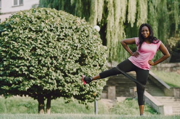 Здоровая молодая африканская женщина на открытом воздухе утром. девушка с ластиком.