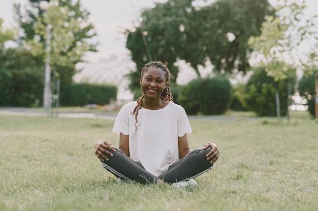 朝の公園で屋外の健康な若いアフリカの女性。ヨガをしている女の子。