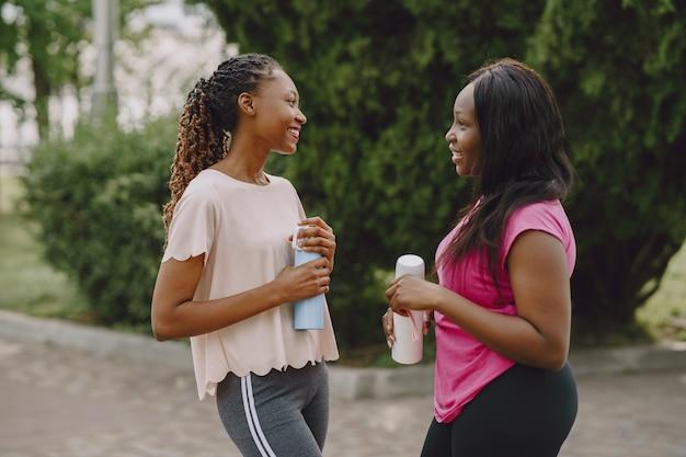 朝の公園で屋外の健康な若いアフリカの女性。友達のトレーニング。