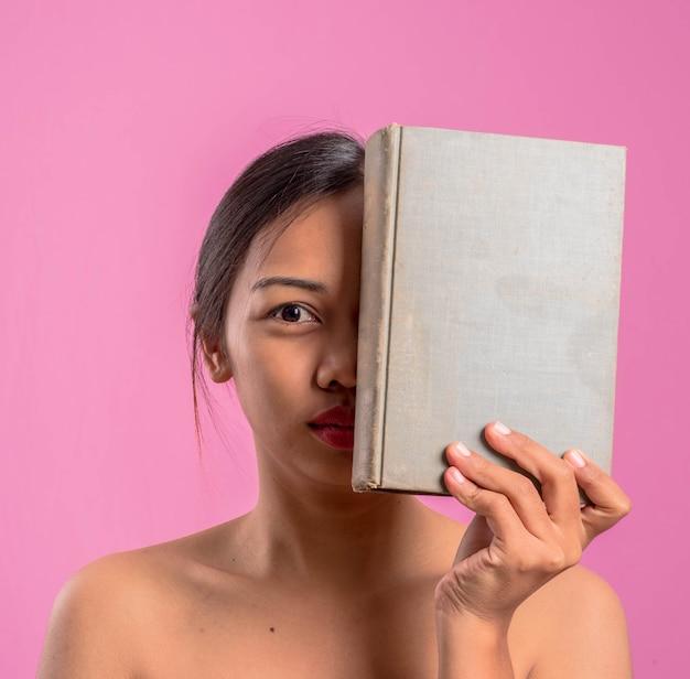 ヴィンテージ本と健康的な若いアジアのラテン女性。