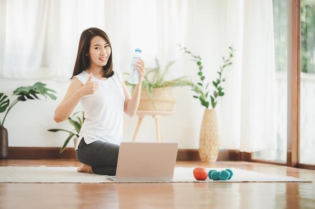 健康な若いアジアの女性は、自宅でオンライン練習ヨガやトレーニングのためにラップトップを使用する準備ができて水のボトルを保持しながら親指を表示します