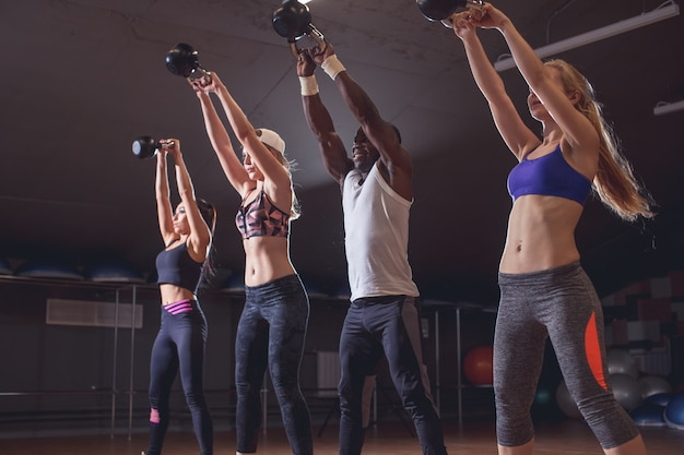 Healthy young athletes doing exercises with kettlebells, at fitness studio.