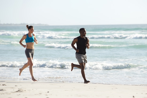 Healthy young couple running on the beach